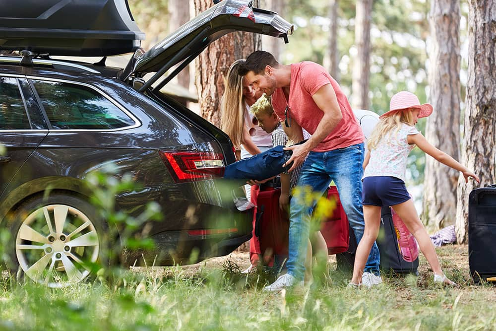 family on camping holiday packing car